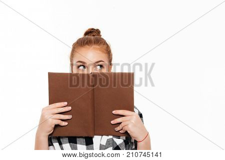Young ginger woman in shirt hiding behind a book and looking away over white background