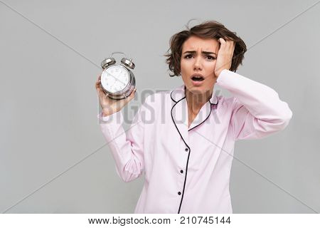 Portrait of a young confused girl in pajamas holding alarm clock and looking at camera isolated over gray background