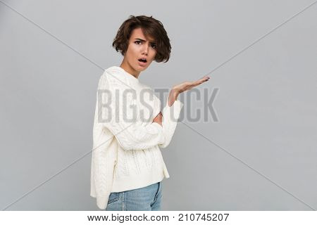Portrait of a confused frustrated girl in sweater pointing away and looking at camera isolated over gray background