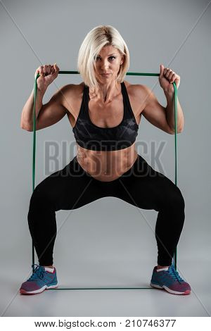 Portrait of strong sports woman doing sit-ups while stretching with elastic rubber, looking at camera, isolated on white background