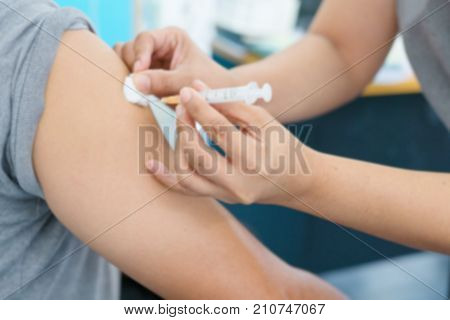Blurry Background of Nurse are vaccinations to patient. To prevent diseases that are prevalent. closed-up of hand with vaccine shot.
