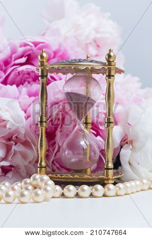 Hour glass, pearls and fresh peony flowers on white leather background