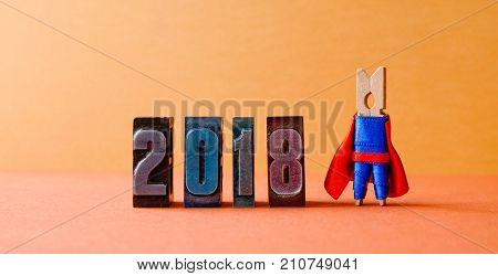 Super successful 2018 new year card. Brave superhero leader posing on vintage letterpress digits. Beautiful clothespin metaphor character in red blue costume
