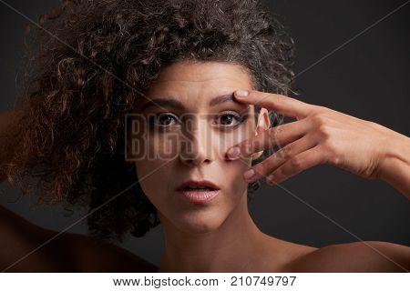 Beautiful young unsmiling woman touching her face