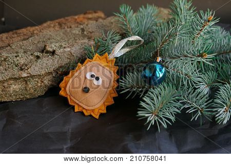 nature tree fir branch with handmade toy from felt on black crafted background