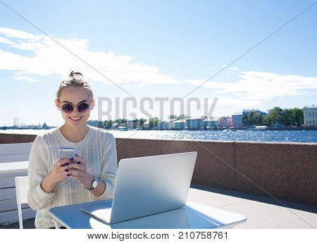 Smiling woman lifestyle writer reading good text message on mobile phone, sitting with laptop computer near embankment river. Hipster girl chatting on cell telephone during work on portable net-book