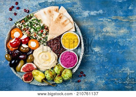 Middle Eastern meze platter with green falafel pita sun dried tomatoes pumpkin and beet hummus olives stuffed peppers tabbouleh figs. Mediterranean appetizer party idea