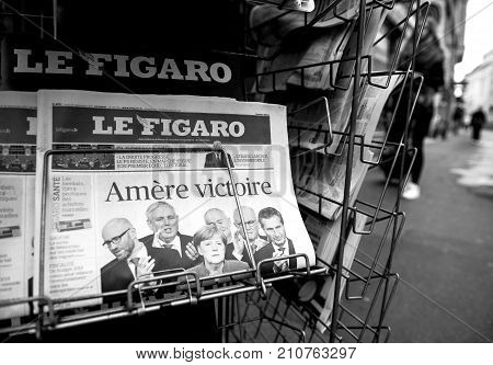 PARIS FRANCE - SEP 25 2017: Le Figaro with Bitter Vitory message about Angela Merkel winning election in Germany for the Chancellor of Germany - black and white street view