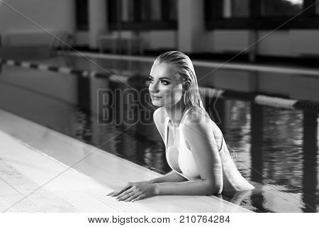 Seductive blonde woman with long wet hair dressed in white swimsuit with low-cut neckline standing in swimming pool and leaning on edge with her hands. Sexy female model emerging from blue water.
