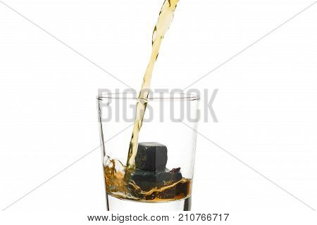 Whiskey pours into a glass with stones.