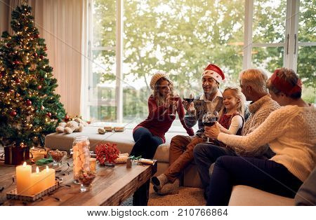 Caucasian family toasting with wine on Christmas eve. Family gathering at home for christmas festival celebrating with wine.