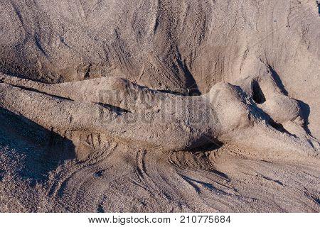 diagonal perspective of romantic and sexy sand sculpture artwork or glyph of a naked woman or mermaid lie in sand on the beach in summer in vacation