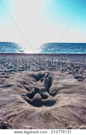 horizont perspective of romantic and sexy sand sculpture artwork or glyph of a naked woman or mermaid lie in sand and sun on the beach in summer in vacation