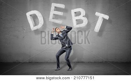 A businessman on a grey background cowers under large concrete letters making a word DEBT above him. Business and finance. Credit and loss. Mortgage conditions.