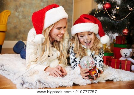 Happy young woman and little girl in Santa's hat playing with snow ball while lying on white carpet at living room