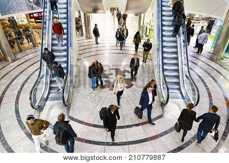 Cabot Place In Canary Wharf With People Up And Down On Escalators .