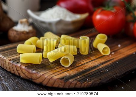 Raw rigatoni pasta on brown wooden board with vegetables around.