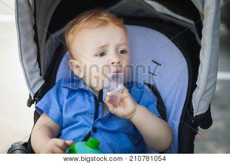 sweet boy blonde boy sitting in pram, cute child playing with his cup in pram