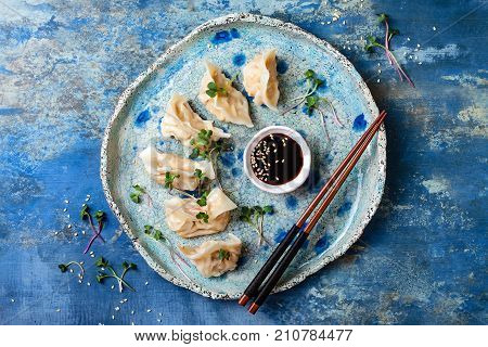 Asian dumplings with soy sauce sesame seeds and microgreens. Traditional chinese dim sum dumplings. Copy space flat lay