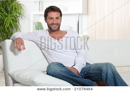 Man relaxing at home sitting on sofa