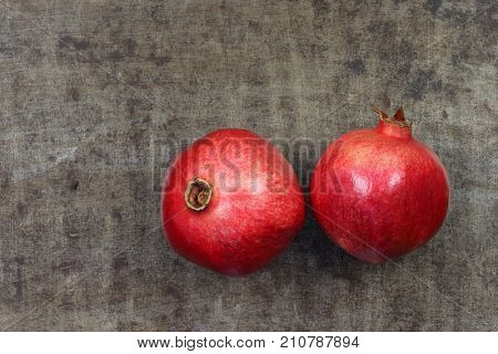 two pomegranate(Punica granatum) on a grungy metal background