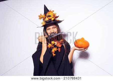 A girl in a Halloween witch costume is going to a Halloween party. The witch is holding a small pumpkin. Big witch hat with autumn leaves