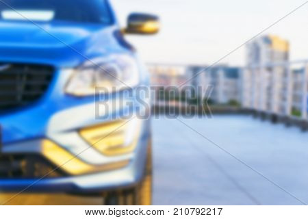 Blurred background with modern luxury car on the blur roof of the building. Modern car exterior details. Soft lightning