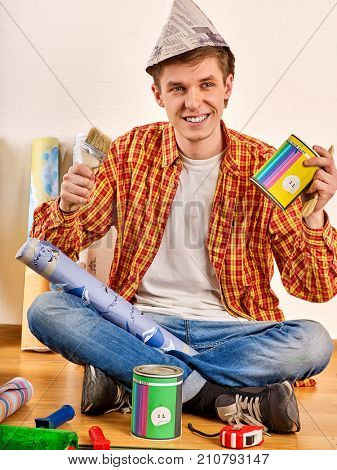 Repair home man holding paint roller for wallpaper. Male in newspaper cap renovation apartment. Paint bank and paint brush in hands. Worker-builder student. Profitable loan repairs.