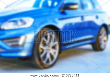 Blurred background with modern luxury car on the blur roof of the building at the sunset. Modern car exterior details. Soft lightning