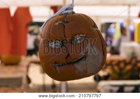 A creepy carved face on a Halloween pumpkin that had a smile before it started rotting and is now a smirk with empty hollow eyes as it hangs on display at a pumpkin patch fall festival. poster