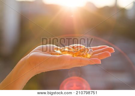 Hand Holding Fish Oil Omega-3 Capsules, Urban Sunset Background.