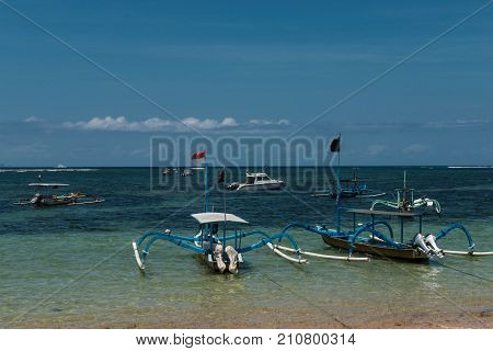 Traditional balinese dragonfly boat on the beach. Jukung fishing boats on Sanur beach, Bali, Indonesia, Asia.
