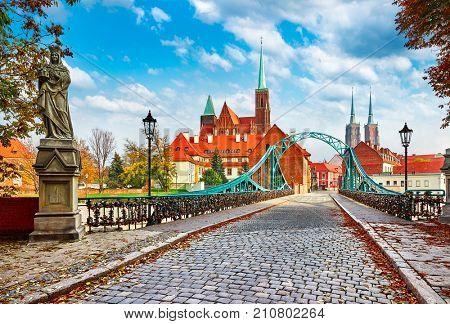 Cathedral Island in Wroclaw Poland green bridge with view on of St John the Baptist picturesque panorama medieval town blue sky and white cloud.