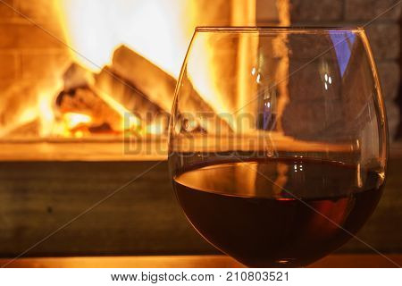 Glass of red wine before cozy fireplace in country house winter vacation horizontal.