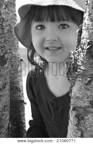 Young Girl Smiling By Trees In Black And White