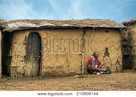 MASAI MARA, KENYA - OCTOBER 17, 2014: African woman from Masai tribe working in front of her village house. The Maasai are a Nilotic ethnic group living in southern Kenya and northern Tanzania.