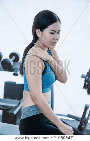 Attractive asian female touching her neck and shoulder in pain Young athletic woman stretching her neck and shoulder