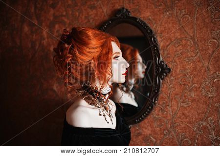 Vampire clothes for Halloween. Girl dress gothic outfit for halloween. Interesting gothic outfit for Halloween. Celebrate Halloween. Prepare an interesting look on Halloween. A woman is a vampire with pale skin and red hair in a black dress and a necklace