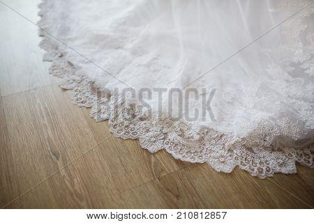 The hem of the wedding dress lies on the wooden floor. Wedding ceremony. Wedding morning of the bride. Fashionable wedding dress. White wedding clothes. Beautiful wedding background. Wedding day