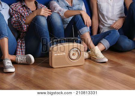 Group of young women with retro radio sitting on floor indoors