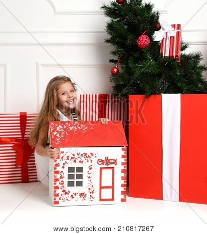 Baby Girl Kid playing with christmas red house in play room at home or kindergarten with little dolls toys and furniture. New year concept