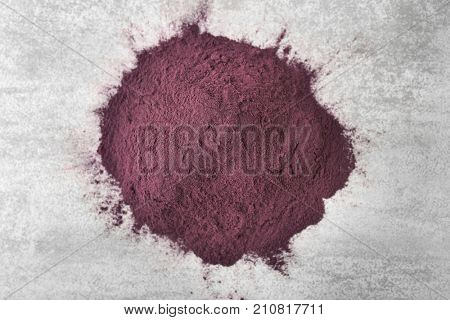 Heap of acai powder on gray background