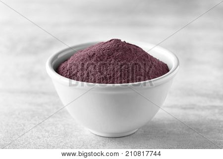 Bowl with acai powder on table