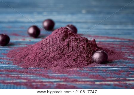 Heap of acai powder and berries on wooden background