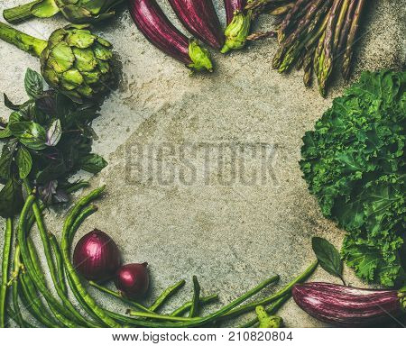 Flat-lay of green and purple vegetables over concrete background, top view, copy space, food frame. Local produce for healthy cooking. Eggplans, beans, kale, asparagus, artichoke, basil. Clean eating