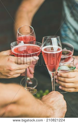Holiday celebration table setting. Friends hands drinking together. People having party, gathering, celebrating with rose champaign, vertical composition
