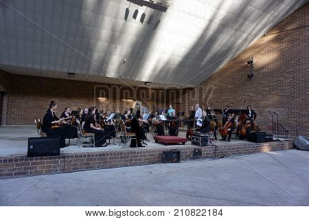 JOLIET, ILLINOIS / UNITED STATES - JUNE 1, 2017: The Metropolitan Youth Symphony Orchestra (MYSO) prepares to perform a free public concert at the outdoor theater in the Billie Limacher Bicentennial Park.