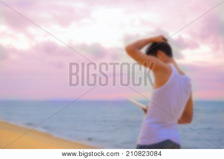 An Asia handsome man wearing white vest standing at the sea using his tablet in his hand to watch seriously bussiness on vocation.By the sky and blue sea as the backdrop with copy space.