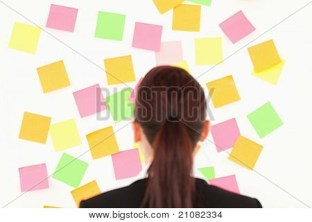 Red-haired woman looking at a wall full of re-positional notes on a white wall