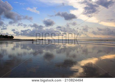 Mirror reflection of the sunset on Kuta beach. The island of Bali. Indonesia.